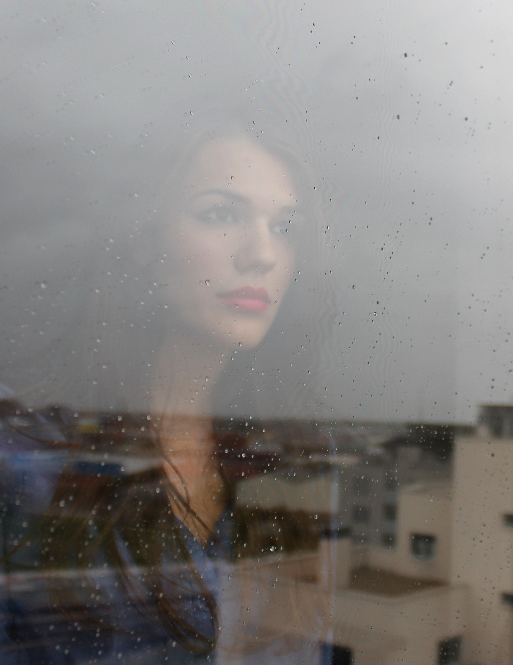brunette looking out window raining jpeg