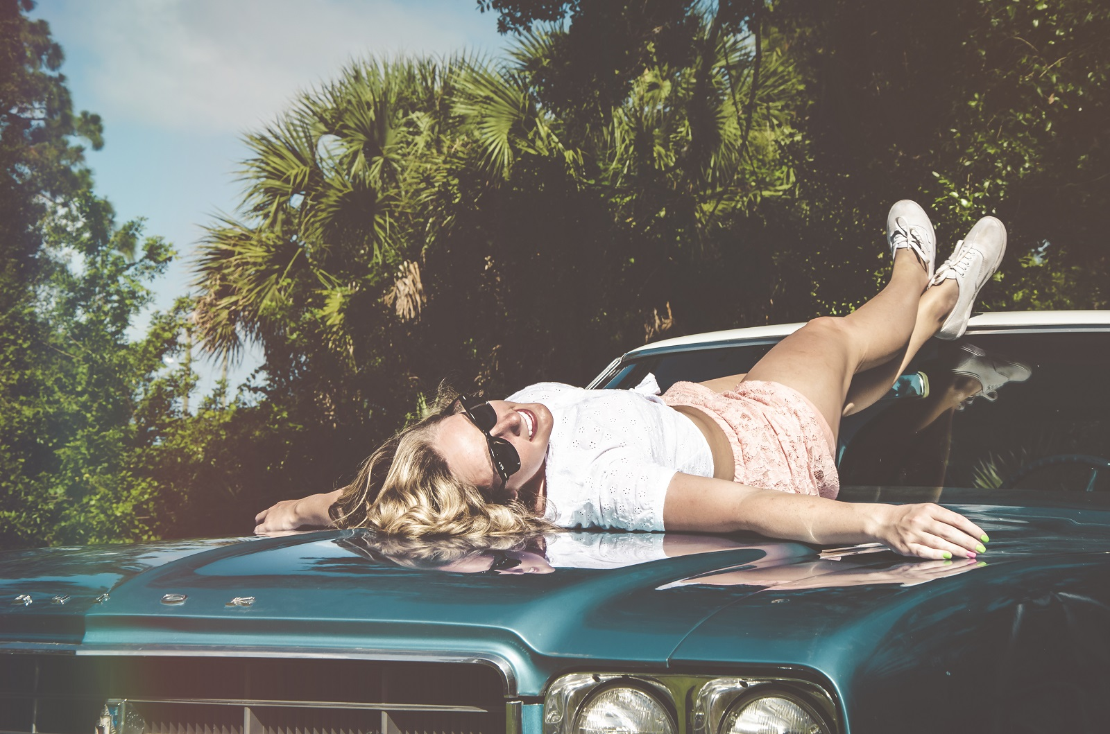 girl   laying   on blue car